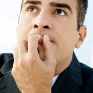 Worried businessman outdoors with finger in mouth, extreme close-up